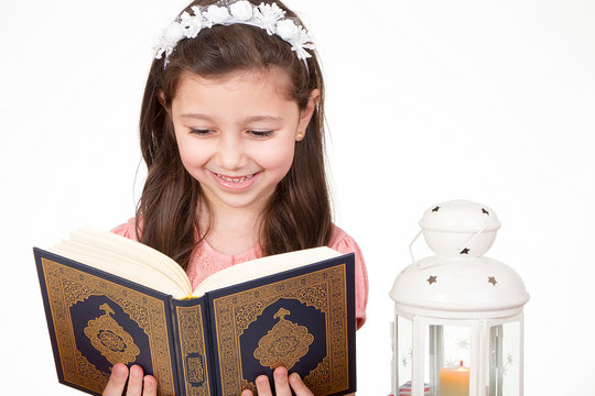 Young Muslim girl reading holy Quran ready for iftar( breakfast ) in Ramadan