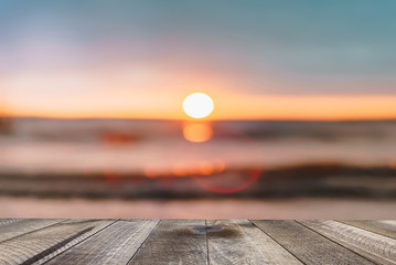 Wooden desk of free space with sea background at sunset.