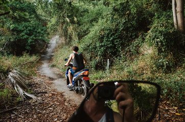 Young man on a scooter driving on a jungle path while another man can be seen through the rear mirror taking a picture of him