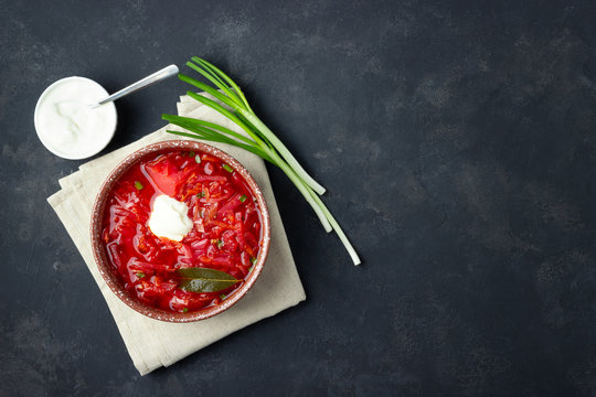 Vegetarian beet red soup - borscht with sour cream on black stone background. Top view.
