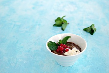 Sweet dessert, chocolate pudding in white portioned saucers on a light blue background. Served with whipped cream and red currant berries. Valentine's Day concept.