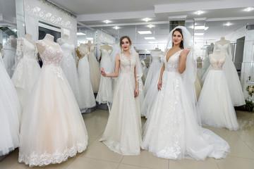 Wedding dresses on two pretty women in salon