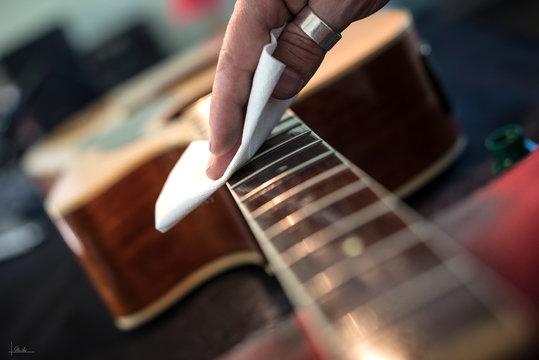 liutaio pulizia tastiera chitarra con panno