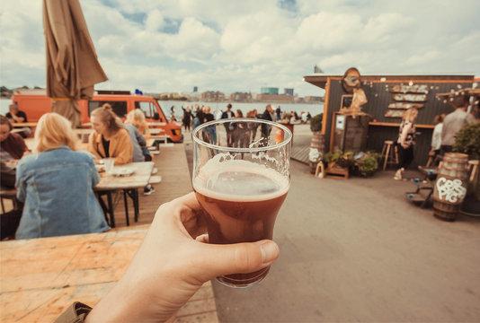 Craft beer glass in drinker hand on street food market of Copenhagen, Denmark. Leisure in Scandinavia with drinks and food of popular city market
