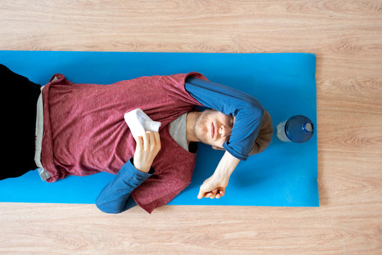young sport man laying on the floor on yoga mat after hard practice f