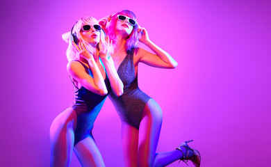 Wall Mural - Fashion. Two DJ girl with Dyed Hair in Colorful neon light enjoy music, friends. Party disco 80s 90s vibes. Model woman in fashionable bodysuit dance, makeup. Creative art, dancing concept