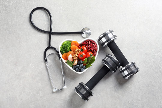 Flat lay composition with bowl of products for heart-healthy diet on grey background