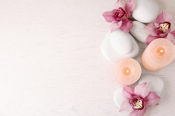 Deurstickers Zen Flat lay composition with zen stones, candles and flowers on wooden background. Space for text