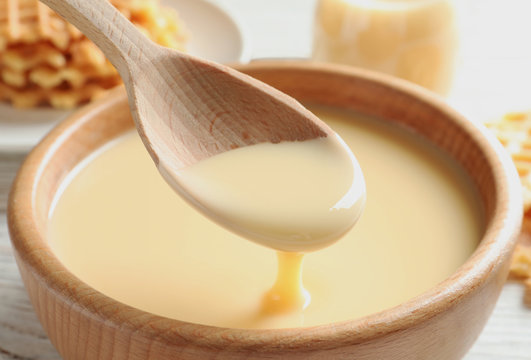 Spoon of pouring condensed milk over bowl on table, closeup. Dairy products