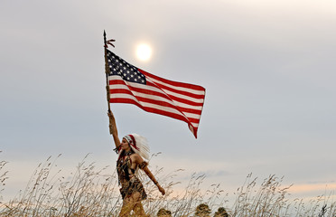 A young woman dresses up as an Indian warrior.  She stands outdoors waving an American flag.  Her facial expression is seen as proud.