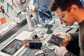 The technician carefully examines the integrity of the internal elements of the smartphone in a modern repair shop Wall mural
