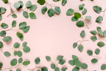 The workspace is decorated with green eucalyptus leaves, floral pattern on a pink background. The apartment lay, top view. Floral frame. Frame of flowers.