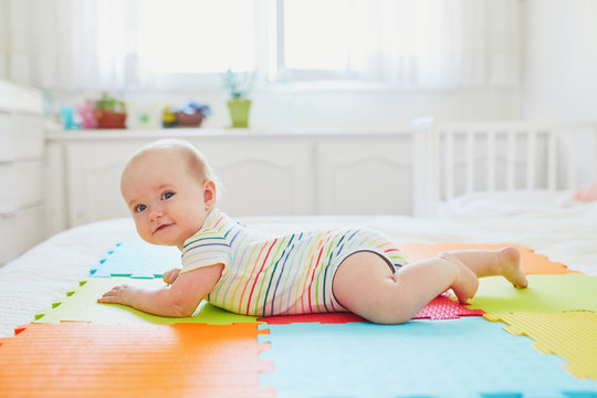 baby girl lying on colorful play mat on the floor
