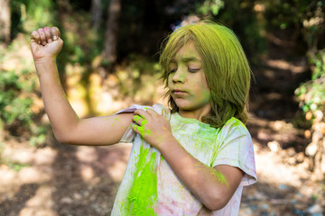 Boy full of colorful powder paint, celebrating Holi, Festival of Colors