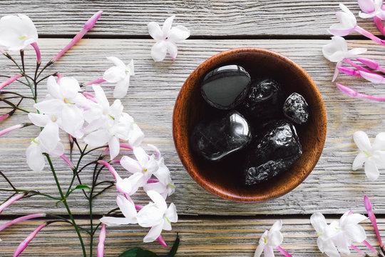 Teak Bowl of Obsidian with Jasmine on White Washed Wood