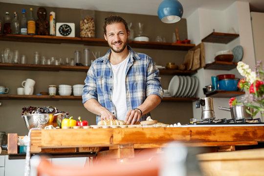 Young man preparing food at home, slicing bread