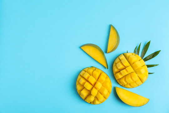 Flat lay composition with cut mangoes and space for text on color background