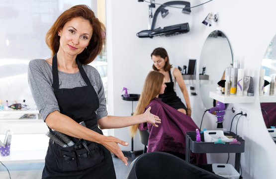 Hairdresser inviting to sit in chair