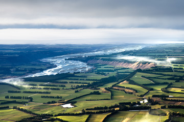 Wide open view over landscape. Patchwork like fields and winding blue river. Canterbury plains landscape. beautiful landscape background. new Zealand outdoors and adventure. Wall mural