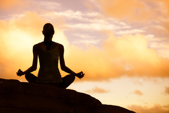 silhouette of woman doing yoga on mountain at sunset