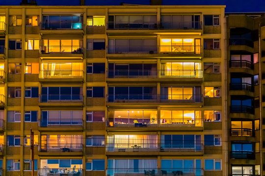 lighted city apartments by night, Belgian city architecture with windows and balconies