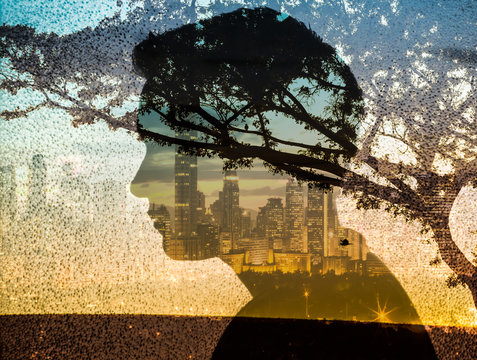 Thoughtful man  silhouette, trees and city skyline, peaceful state of mind concept