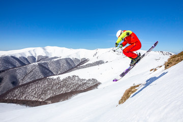 Fototapete - A skier is riding and jumping at mountain terrain. A wonderful sunny day