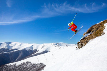 Wall Mural - A skier is riding and jumping at mountain terrain. A wonderful sunny day