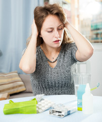 Confused  woman sitting among pills