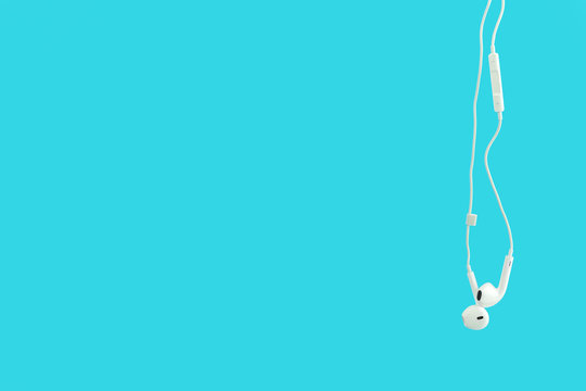 White hanging ear buds headphones isolated on a blue