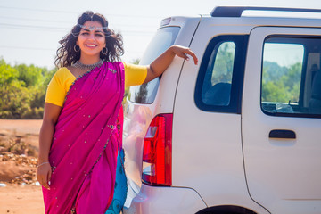 relaxed indian woman in a traditional pink sari and costume jewelry on summer travel vacation to the coast towards the sea