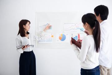 グラフの説明をする女性マネージャー