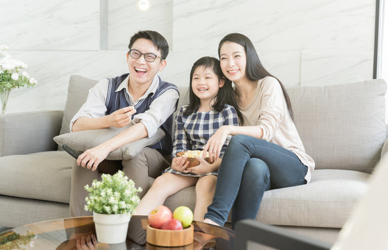 happy asian family watching tv together on sofa in living room. family and home concept
