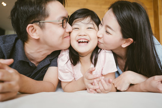 Asian Parents kissing their little daughter on both cheeks. family portrait.