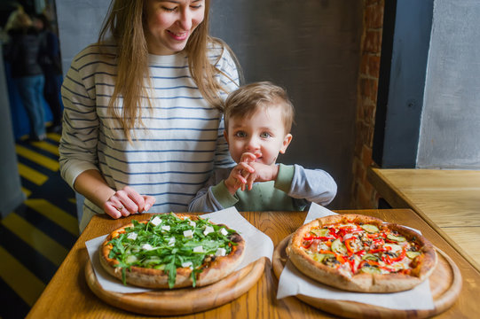 A family portrait of mother and little child eating pizza in restaurant.