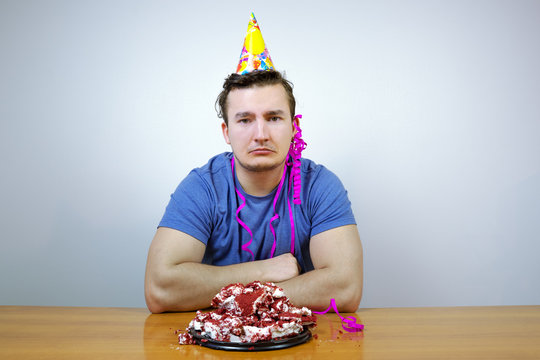 Sorrorful man with birthday party cone hat on head and crumple cake,  crying. guy in bad mood while having celebration.