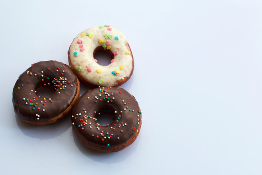 American donuts, glazed with melted chocolate and decorated with sprinkling, lie on a platter.