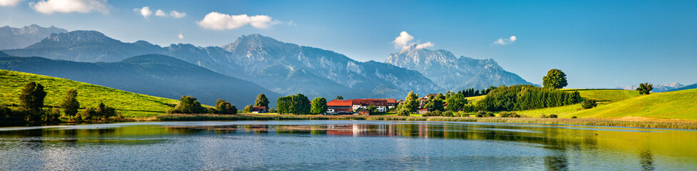Panoramic bavarian landscape with small village by a lake, the alps behind, Allgau, Bavaria, Germany Fototapete