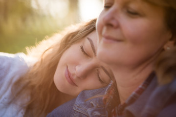 Love - senior mother with her teen daughter outdoors