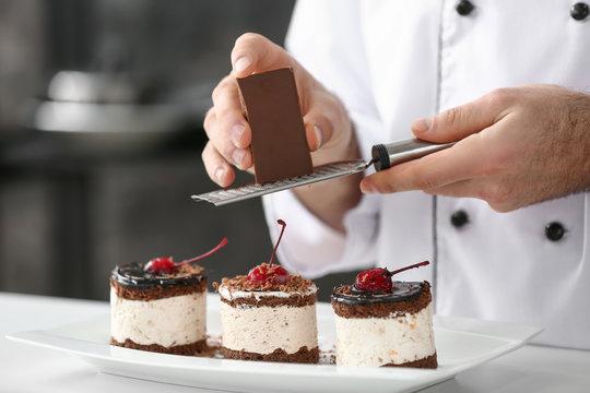 Male confectioner decorating tasty dessert in kitchen, closeup