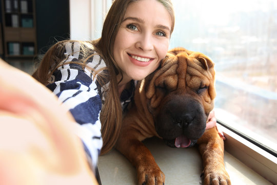 Woman taking selfie with her cute funny dog near window