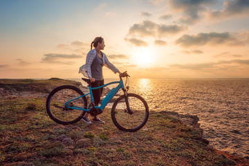 Woman with a bike in the nature / Morning view of a woman with a bike enjoys the view of sunrise at the rocky Black Sea coast