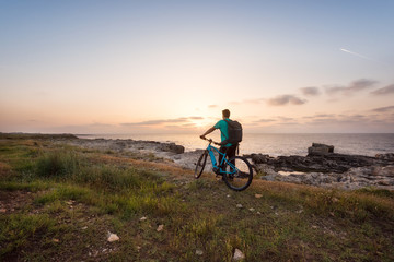 Man with a bike in the nature / Rear view of a man with a backpack and a bike enjoys the view of sunrise at the Black Sea coast