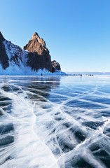 Winter landscape of frozen lake Baikal. Olkhon Island in March. Many tourists come to visit the famous Cape Khoboy, go ice-skating on smooth ice and take pictures against the background of ice cliffs