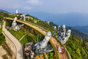 Top aerial view of the famous Golden Bridge is lifted by two giant hands in the tourist resort on Ba Na Hill in Danang, Vietnam.