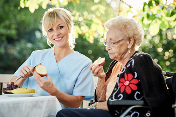 Pflegerin hilft Seniorin beim schälen von Obst