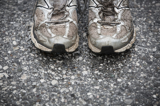 Worn, dirty, smelly and old running shoes on a tarmac road.