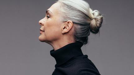Senior woman on grey background