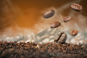 Close up Coffee beans Coffee beans dropping in to  the cofee powder with smoke