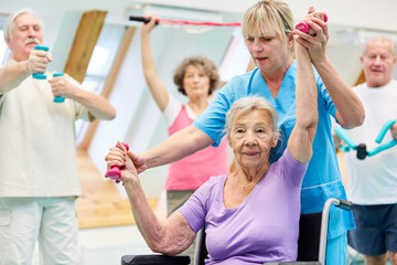 Alte Frau trainiert mit Hanteln im Reha Kurs